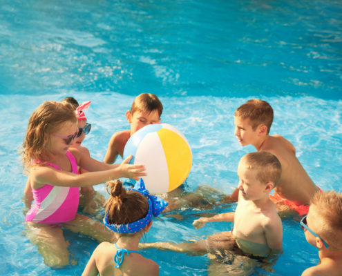 young kids playing with a beach ball in the pool