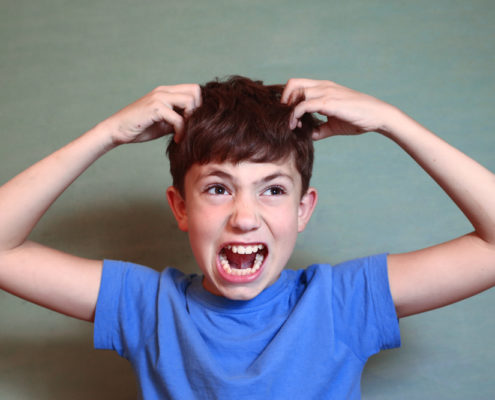 Young boy is upset he needs a head check because he may have lice wearing a blue t-shirt